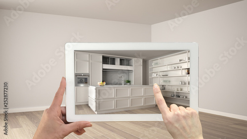 Fototapeta Augmented reality concept. Hand holding tablet with AR application used to simulate furniture and design products in empty interior with parquet floor, classic white kitchen obraz