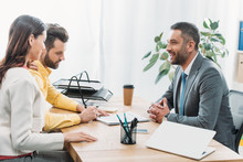 Advisor And Woman Sitting At Table Wile Investor Signing Document In Office