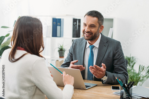 Photo selective focus of advisor sitting at table with laptop and woman in office