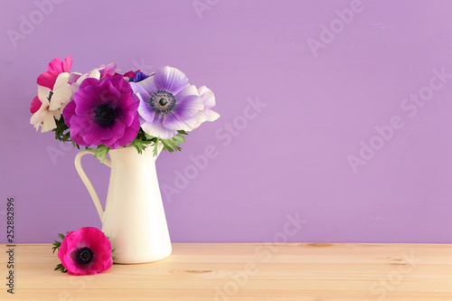 Valokuvatapetti spring bouquet of colorful anemones in the vase over wooden table