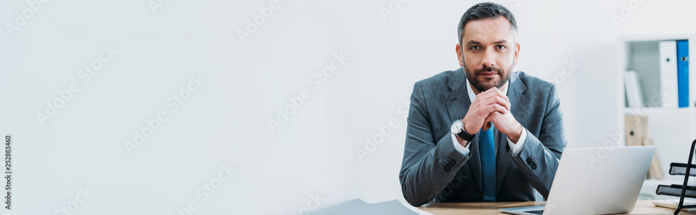 Fototapety, obrazy: businessman sitting at table with laptop and looking at camera in office