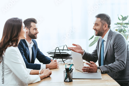 Fotomural handsome advisor in suit talking with investors at workplace