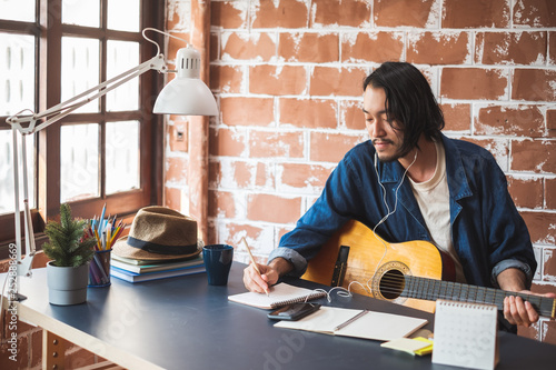 Photo Asian man musician writing song with guitar