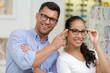 couple is choosing glasses in optics store