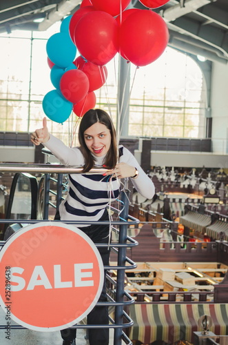 Photo  Young pretty woman holding red baloons in an indoor market hall
