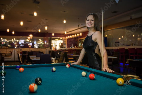 Obraz na plátně Beautiful woman in black dress posing with billiard cue