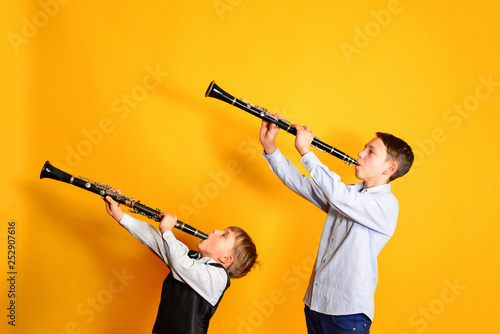 Foto Two children playing the clarinet, on a yellow background