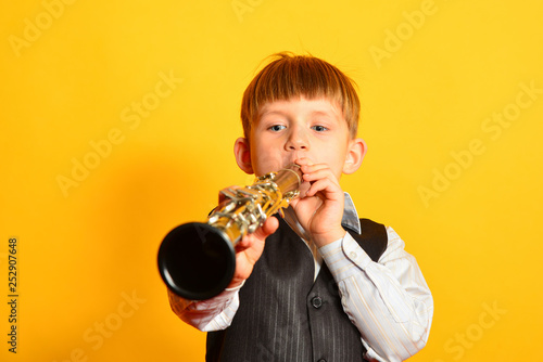 A little boy in a suit plays the clarinet Fototapeta