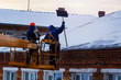 Workers in overalls and orange helmets on the crane basket remove icicles from roof of the house on a winter day - cleaning the roofing, utility service, safety, top view