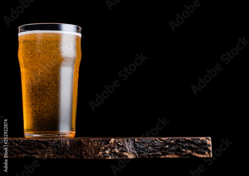 Photo  Glass of lager beer with foam and bubbles on vintage wooden board on black background