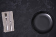 Empty black plate and cutlery on a black background, top view.