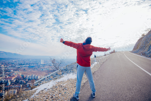 Fotografia  Strong male in his 20s stretching in the morning at winter while looking at his hometown in the valley