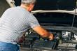 Senior man fixing his car