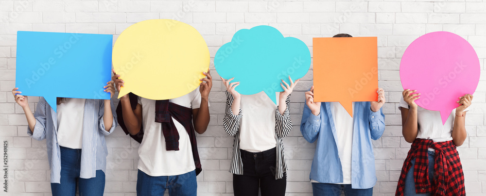 Fototapeta Teenagers holding speech bubbles with copy space