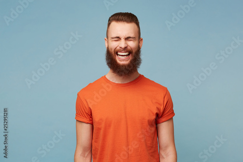 Isolated shot of joyful young cute man laughs joyfully as hears funny anecdote from friend, has heavy beard, poses against blue studio wall Canvas Print