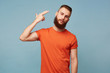 canvas print picture - Portrait of young bearded man committing suicide with finger gun gesture. Portrait of despaired guy shooting himself making finger pistol sign against blue wall background. Human face expressions