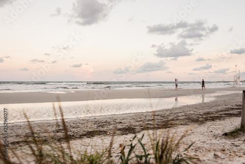 Fotografia, Obraz  Coppia adulti gioca a racchette sulla spiaggia al mare al tramonto