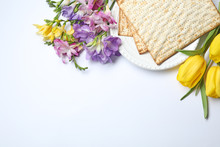 Composition With Matzo And Flowers On White Background, Top View. Passover (Pesach) Seder