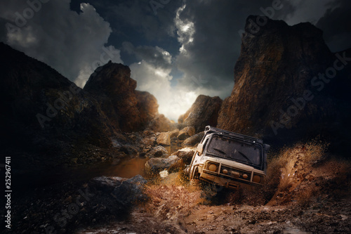 Fotografie, Obraz  4x4 off road vehicle coming out of a mud hole hazard,mud and water splash in off-road racing on mountain road