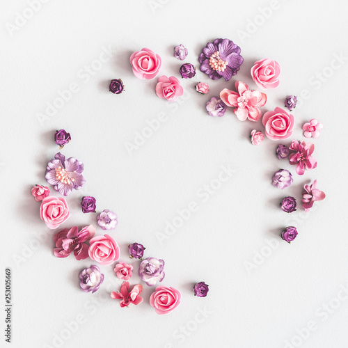 Flowers composition. Wreath made of purple and pink flowers on pastel gray background. Flat lay, top view, copy space, square