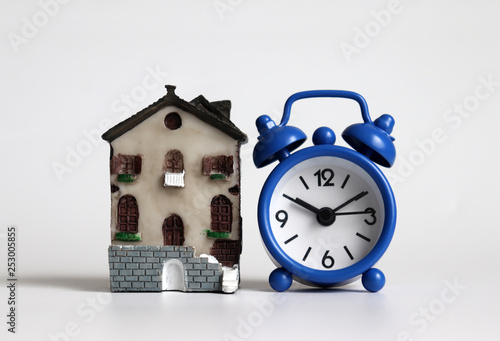 Fotografía  A miniature house and a blue alarm clock.