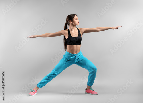 Sporty young woman on light background