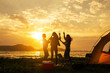 Silhouette Group of women party and dancing with drink bottles enjoy travel camping,trekking in vacation time at sunset.