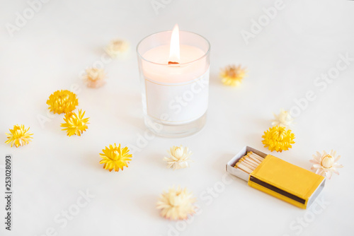 Wooden wick candle with matches and yellow flowers Canvas Print