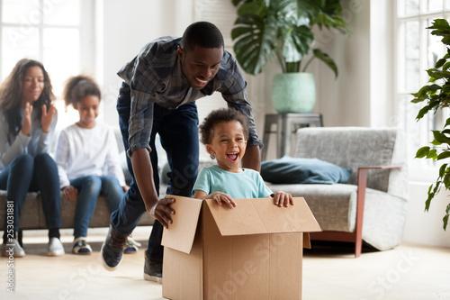 Fototapeta Happy black family play with kids moving to new home obraz