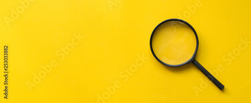 close up magnifier glass on yellow background Wallpaper Mural