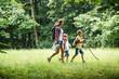 Leinwandbild Motiv Mother and her little sons hiking trough forest .