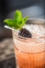 Cocktail Drink Bramble With Black Berries And Mint At Barcounter In Night Club Or Restaurant
