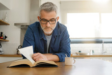 Man Reading Book At Home In Modern Kitchen