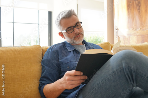 Valokuva Man in 40s reading book in modern home
