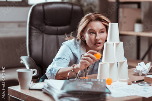 Stressed businesswoman feeling relieved playing with tennis ball - 253058087
