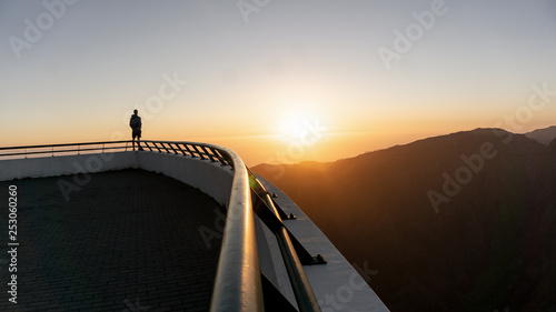 Fototapeta  Hiker stands on the sharp corner and enjoys the beautiful view at sunset