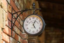 Old City Street Clock On A Hou...