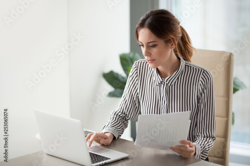 Obraz Serious focused businesswoman typing on laptop holding papers preparing report - fototapety do salonu