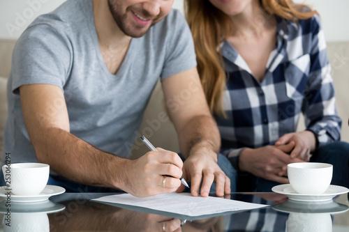 Tenants write signature on rental sale agreement, close up view - fototapety na wymiar