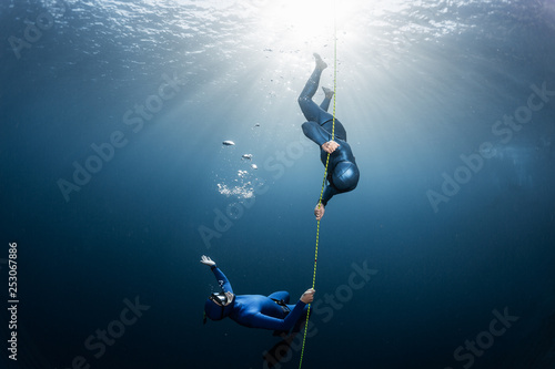Photo Two freedivers play with bubbles near the rope