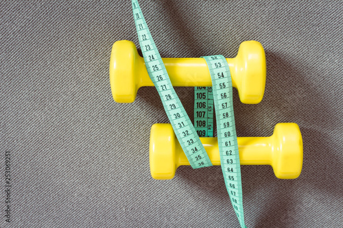 Fotografia  Yellow dumbbells and green measuring tape on grey fitness mat