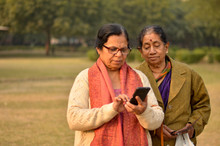 Senior North Indian And South Indian Women Looking In A Smartphone In A Park In Delhi Winters