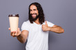 Portrait of his he nice cool attractive cheerful cheery wavy-haired guy giving takeaway cup showing thumbup isolated over gray violet purple pastel background
