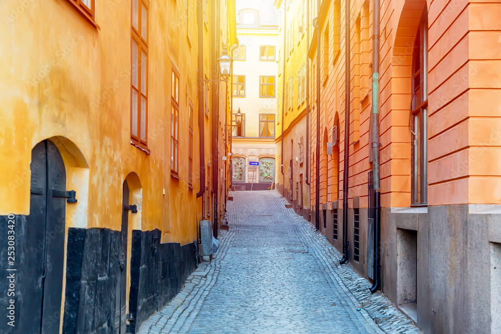Fototapety, obrazy: The narrow cobblestone street with yellow medieval houses of Gamla Stan historic old center of Stockholm at summer sunny day.