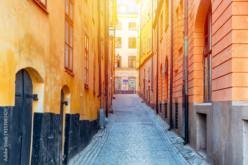 The narrow cobblestone street with yellow medieval houses of Gamla Stan historic old center of Stockholm at summer sunny day.