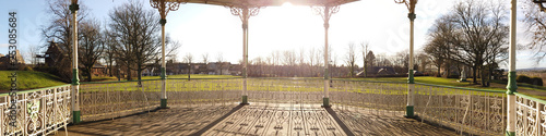 Photo One hundred and eighty degree panorama of shadows cast by a low sun of the railings of a bandstand in a park