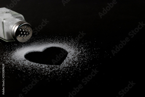 Foto World kidney day, White salt formed heart picture on black paper background with copy space for advertisers