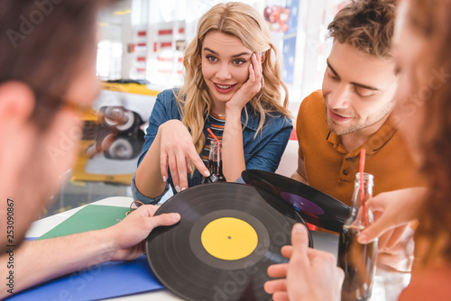 selective focus of smiling, handsome and beautiful friends talking and holding vinyl at cafe - 253090867
