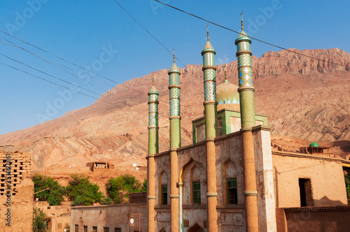 The facade of the mosque at the Uyghur village of Tuyog, with mountains on the background, Xinjiang region, China Wallpaper Mural