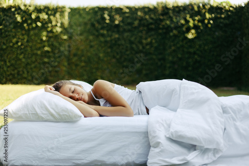 Foto  Girl sleeping on matress on grass